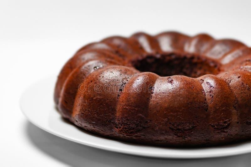 Chocolate bunt cake whole sponge on a plate white background closeup royalty free stock image