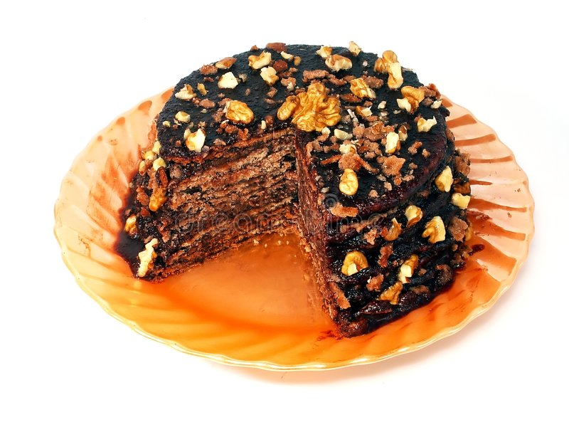 Chocolate Cake. Piece of home made chocolate cake on the orange plate. It's made of sweet wafers smeared with cacao cream. Top is covered by chocolate icing with stock image