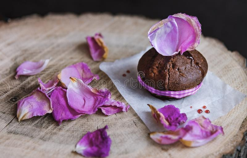 Chocolate cake on a baking paper served with rose petals on a wooden sevice plate, close up. stock image