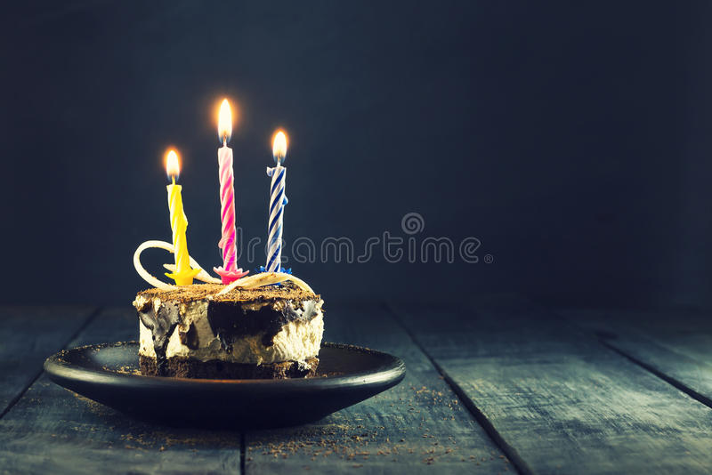 Chocolate cake with a candle and gifts.Happy Birthday, card. Holidays greeting card. Wooden dark blue background stock image