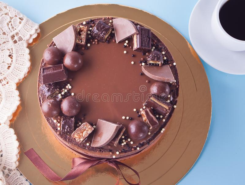 Chocolate cake with candy and ribbon on a blue table royalty free stock photography