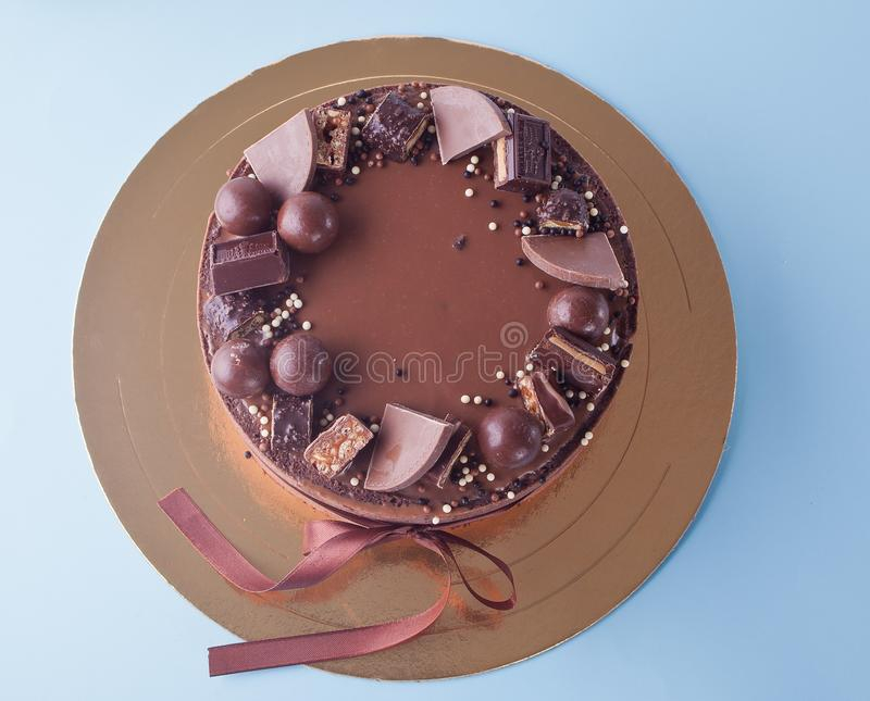 Chocolate cake with candy and ribbon on a blue table. Top view royalty free stock images