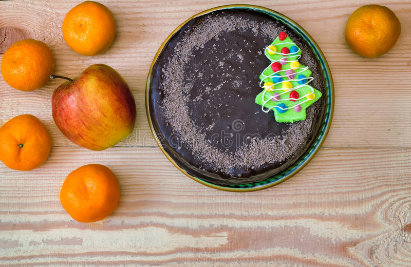 Chocolate cake on a ceramic dish on white background. A big chocolate cake with decoration in the form of a Christmas tree on a ceramic platter. Presented on a stock photos