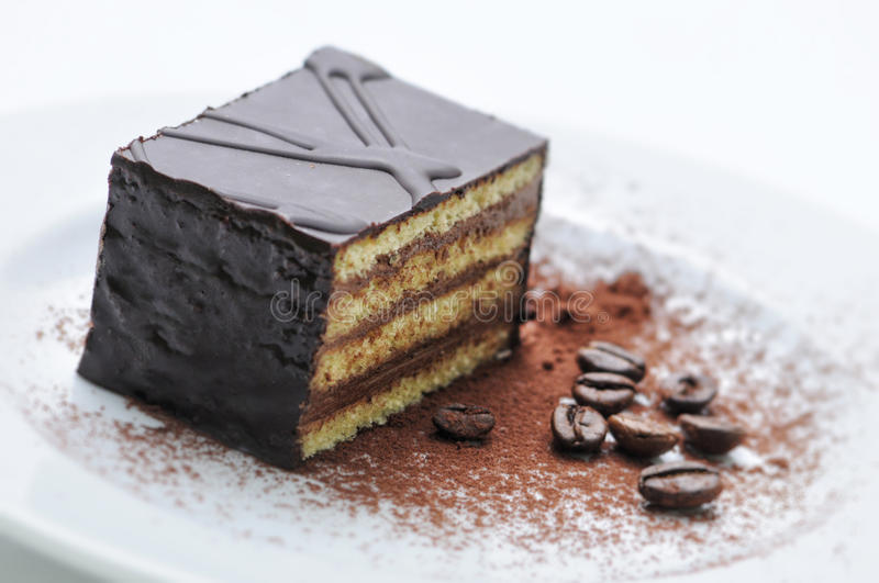 Chocolate cake with coffee beans on white plate, sweet dessert, patisserie, shop, cocoa powder stock image