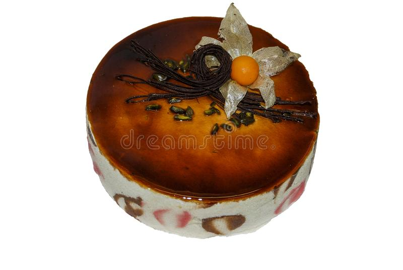 Chocolate cake covered with caramel sauce and decorated with physalis flower royalty free stock images