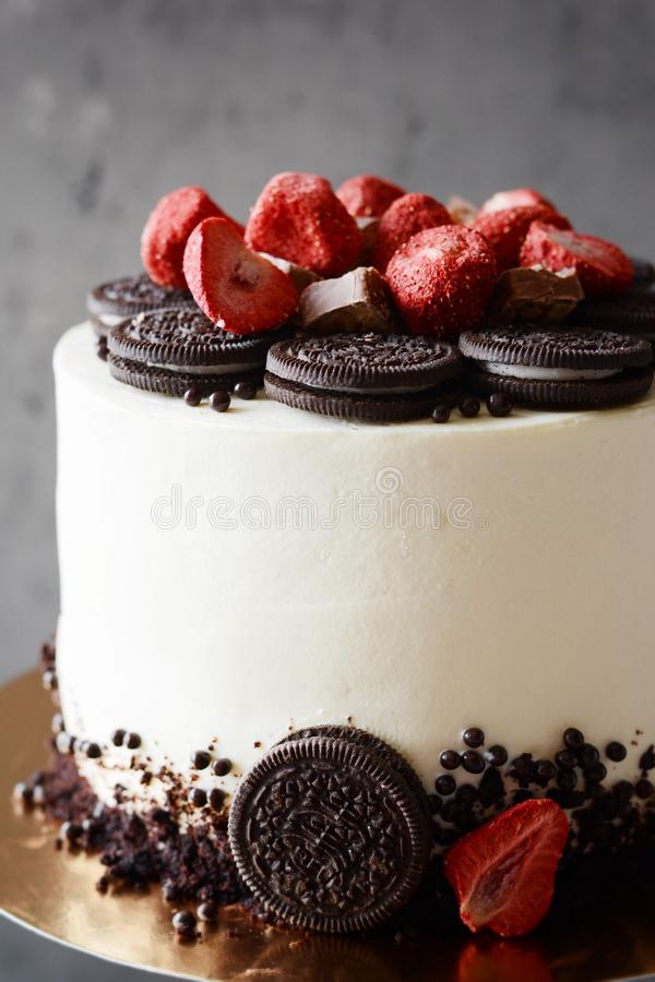 Chocolate cake with cream cheese filling and Oreo chocolate cookies with freeze-dried strawberries on a dark background. Tall cake on a wooden black cake plate stock image