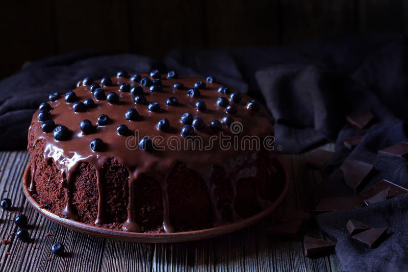 Chocolate cake decorated with blackberries on vintage wooden table background stock image