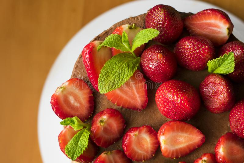 Chocolate cake decorated with fresh strawberries and mint leaves. Cooking. Chocolate cake decorated with fresh strawberries and mint leaves. Cooking stock photos