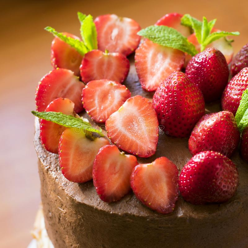 Chocolate cake decorated with fresh strawberries and mint leaves. Cooking. Confectionery stock photo