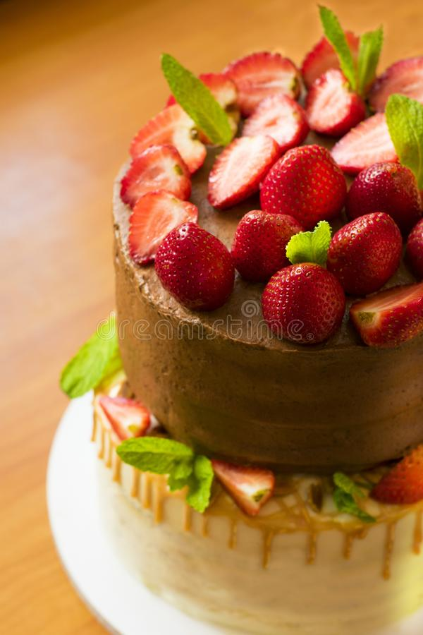 Chocolate cake decorated with fresh strawberries and mint leaves. Cooking. Confectionery royalty free stock image