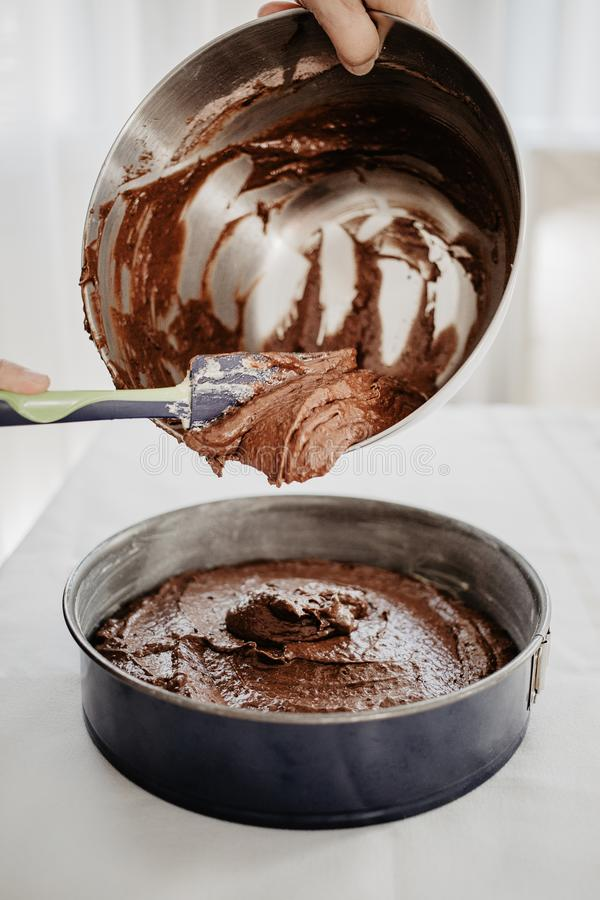 Chocolate cake dough being transferred into round-shaped tin royalty free stock image