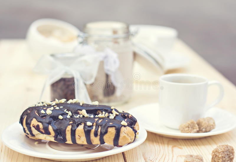 Chocolate cake (eclair) with cup of coffee. stock photography