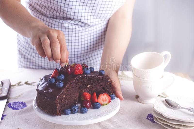 Chocolate cake with fresh berries, on white background. A girl is holding a cake in her hands. Sweet dessert. Copy space royalty free stock images