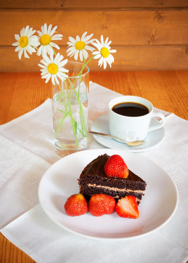 Chocolate cake with fresh strawberry and a cup of coffee stock images