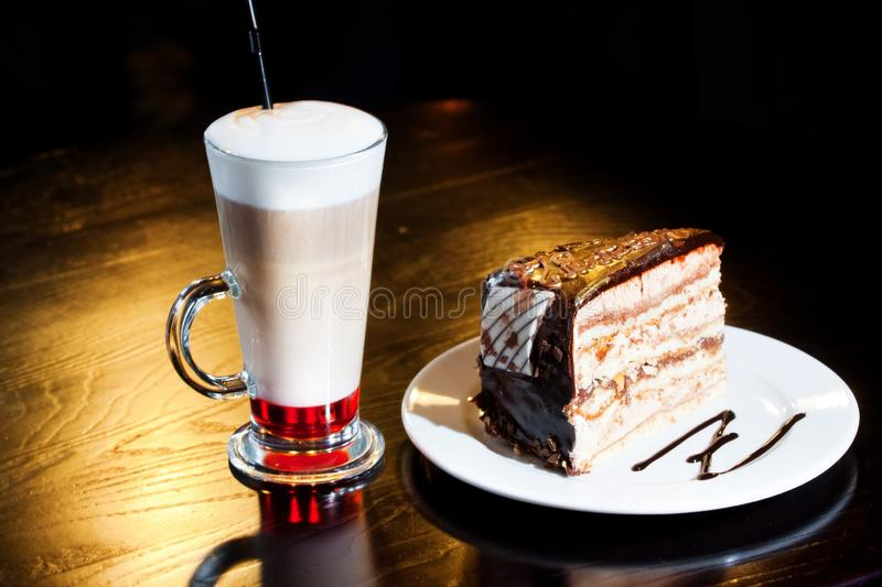 Chocolate cake and latte with syrup served on a wooden table in cafe, delicious food photo stock photos