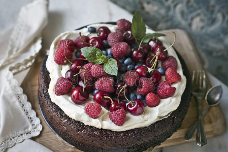 Chocolate cake with mascarpone on rustic background with raspberries, cherries, blueberries and mint leaves. stock photography