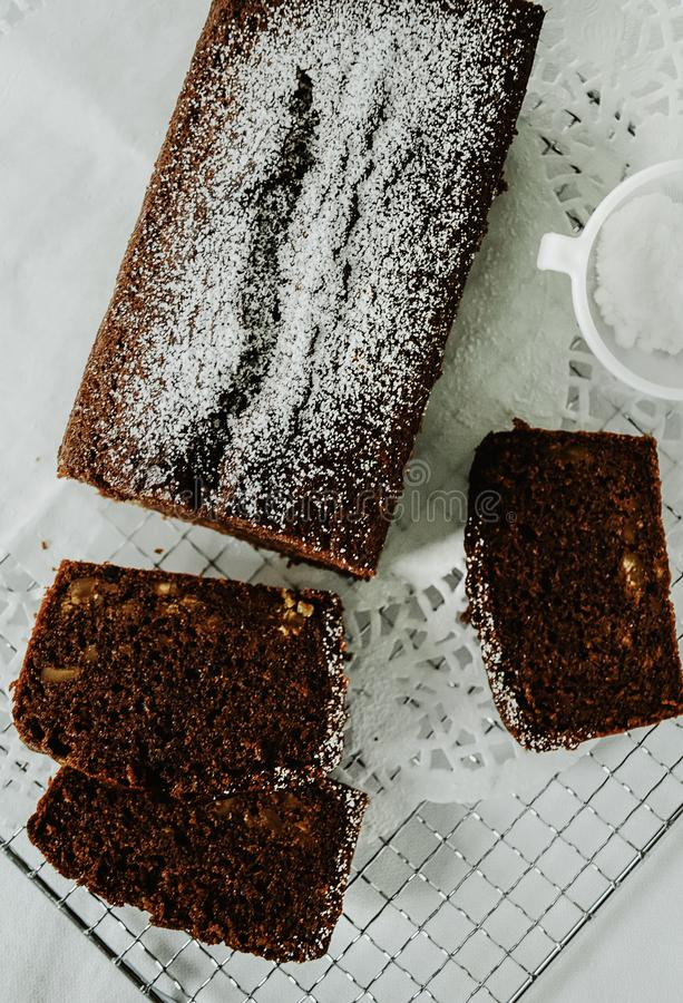 Chocolate cake with nuts inside cut into slices on cooling rack. stock images