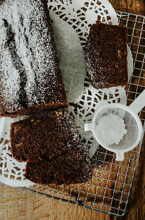 Chocolate cake with nuts inside cut into slices on cooling rack. royalty free stock photo