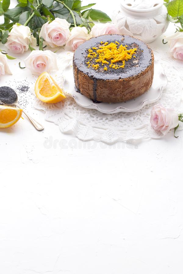Chocolate cake with orange and icing. On a white background, and a bouquet of white roses. Good morning with a surprise and stock photography