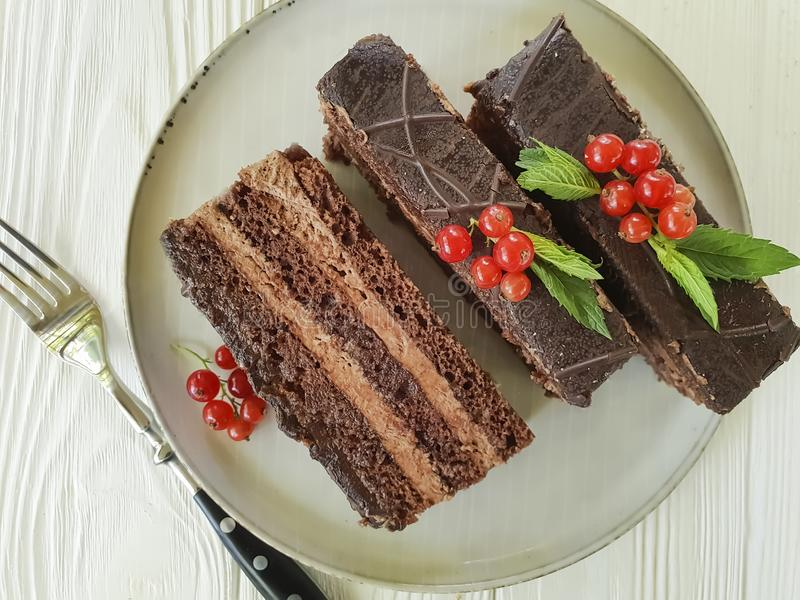 Chocolate cake, red currant, mint cutting dish seasoning pastry plate on white wooden. Chocolate cake red currant mint plate dish on white wooden pastry royalty free stock photos