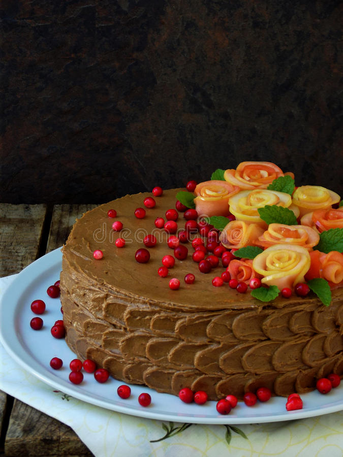 Chocolate cake with roses made from apples and cranberries royalty free stock photo