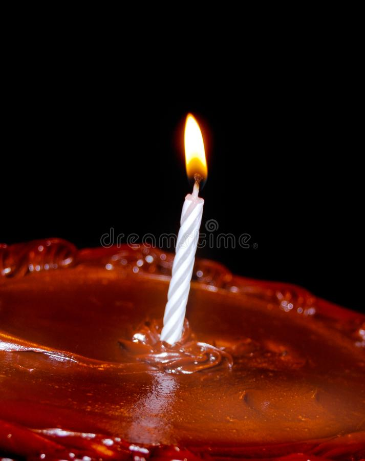 Cake with Lit Candle Vertical Black Background. Chocolate cake with a single Burning Birthday Candle. Background black. Room for copy space. Vertical royalty free stock image