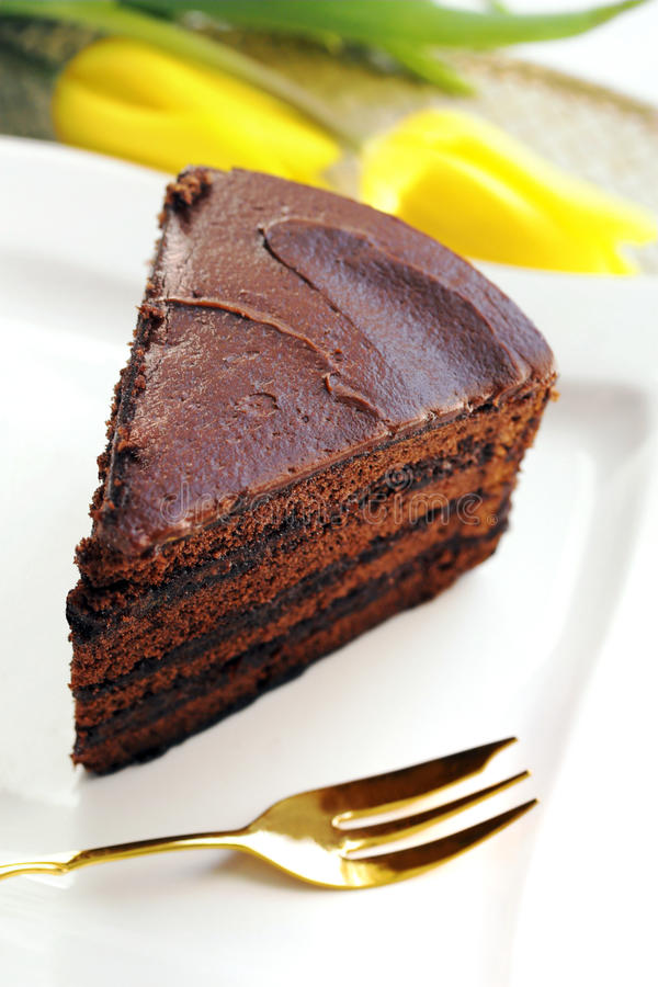 Chocolate cake slice. With yellow tulips in background stock photos