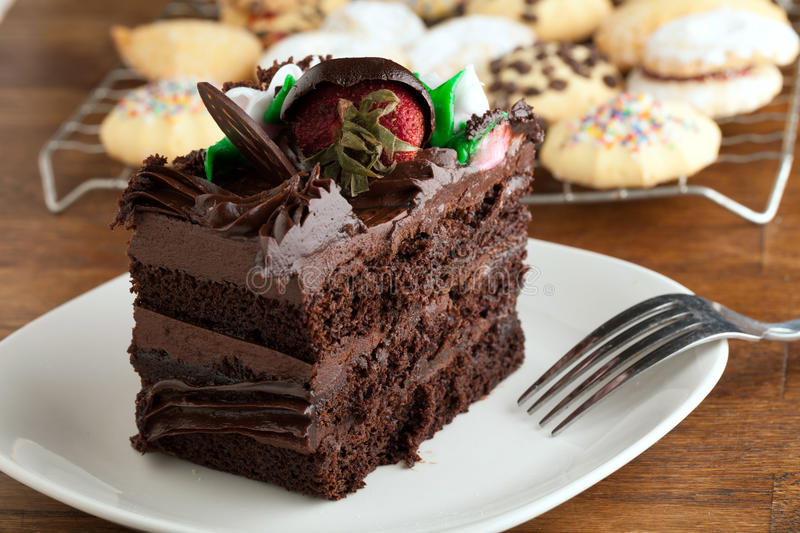 Chocolate Cake Slice with Cookies. Italian cookies and a decadent slice of chocolate cake with iced flowers and chocolate covered strawberries on a plate with a royalty free stock photos
