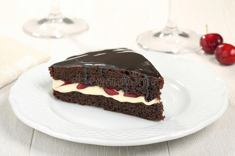 Chocolate cake on white ceramic plate. Dessert chocolate cake with creama and cherry on plate stock photos