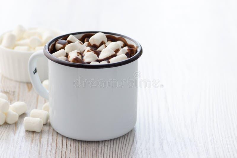 Chocolate caliente con las melcochas en una taza del metal blanco fotos de archivo