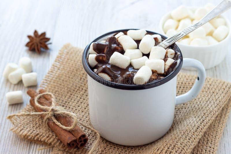 Chocolate caliente con las melcochas en una taza del metal blanco imagenes de archivo