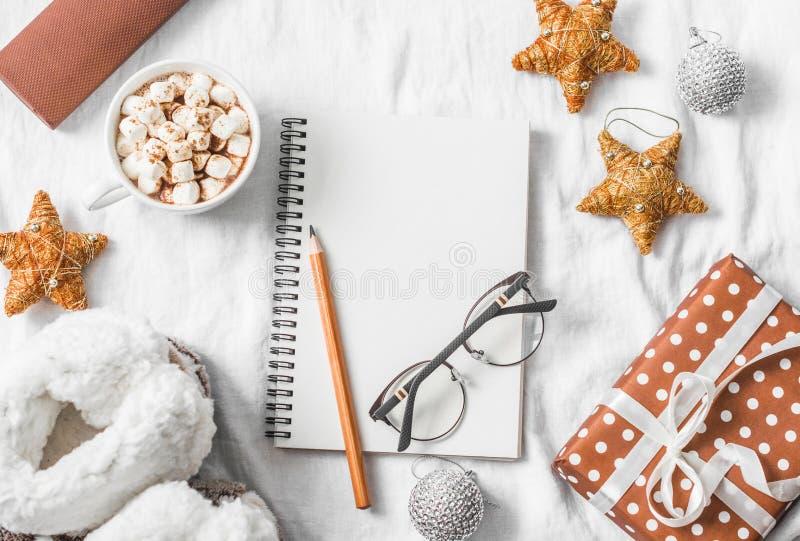 Chocolate caliente con las melcochas y el canela, libreta en blanco limpia, caja de regalo en un fondo ligero Planeamiento de la  foto de archivo libre de regalías