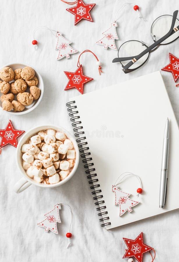 Chocolate caliente con las melcochas y el canela, libreta en blanco limpia, decoraciones de la Navidad en un fondo ligero Inspira fotos de archivo libres de regalías