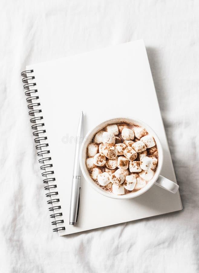 Chocolate caliente con las melcochas y el canela, libreta en blanco limpia en un fondo ligero Planeamiento de la inspiración de l imagen de archivo libre de regalías