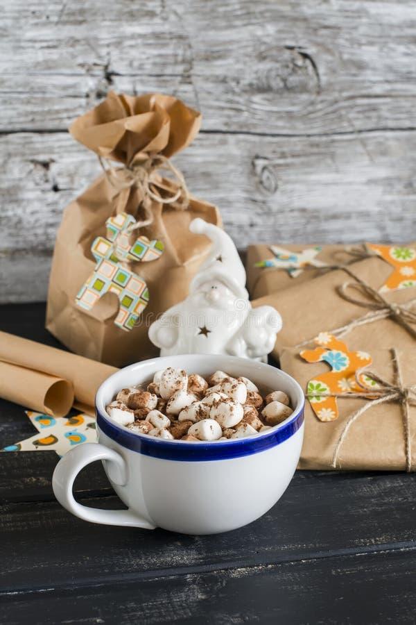 Chocolate caliente con las melcochas y los regalos hechos en casa de la Navidad en superficie de madera foto de archivo