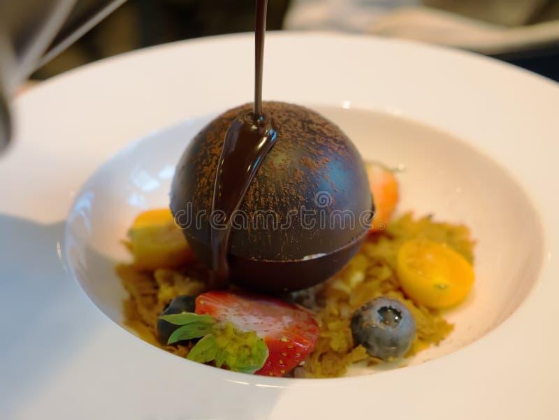 Chocolate caliente de colada en la esfera del chocolate imagenes de archivo