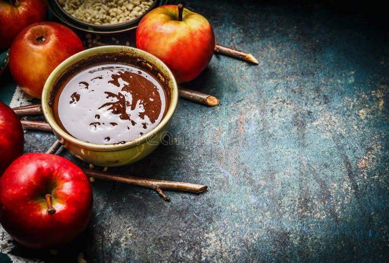 Chocolate caliente en cuenco y manzanas rojas con las ramitas, ingredientes para las manzanas dulces que hacen, preparación en fo fotos de archivo