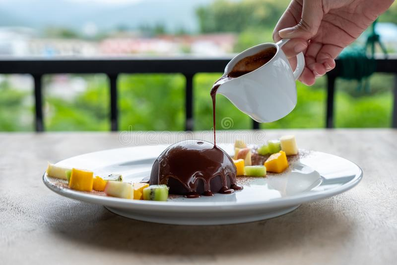 Chocolate caliente que vierte en el postre de la bóveda del cacao con las frutas de las rebanadas foto de archivo libre de regalías