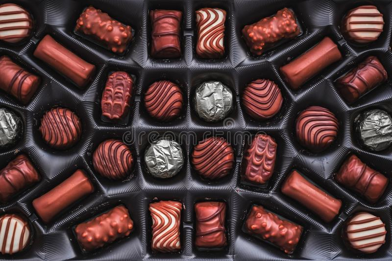 Chocolate candies in the box with silver foil stock images