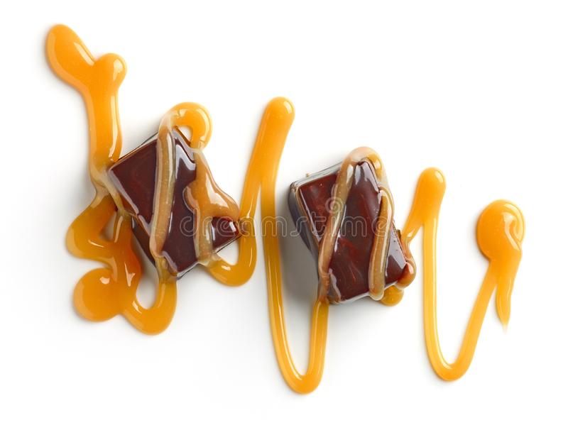 Chocolate candies and caramel sauce. Isolated on white background, top view royalty free stock image