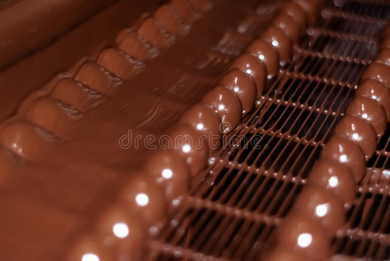 Chocolate candies on the conveyor of a confectionery factory close-up. Chocolates just poured with liquid chocolate on a conveyor belt of a confectionery factory stock photos