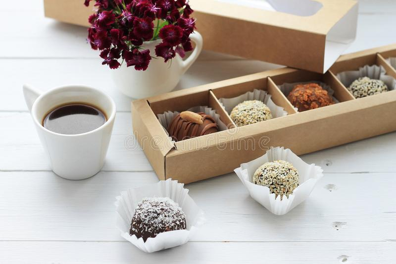 Chocolate candies, a cup of coffee and a bunch of flowers for Valentine`s Day on wooden table royalty free stock photo
