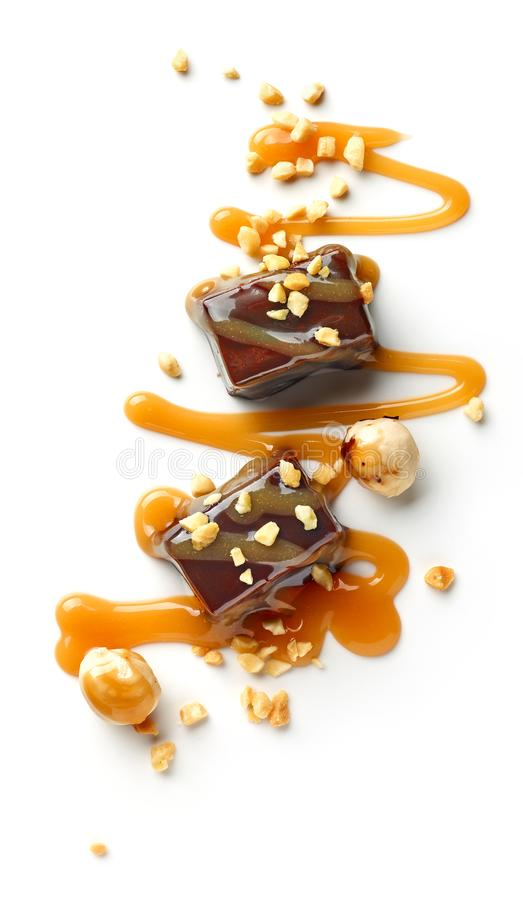 Chocolate candies decorated with caramel sauce and nuts. Isolated on white background, top view stock photos