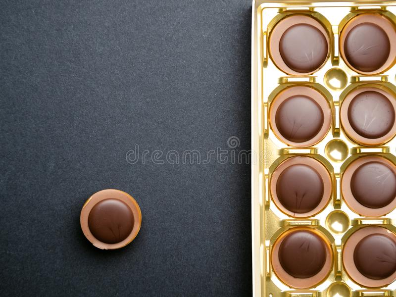 Chocolate candies in a gold box over black background, top view royalty free stock image