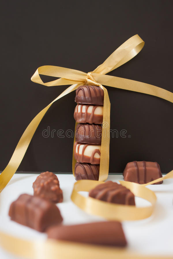 Chocolate candies. Tower of chocolate candies tied with a gold ribbon on a black background royalty free stock images