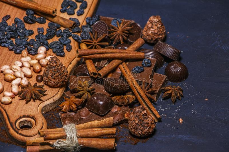 Chocolate, chocolate candies, truffles, cinnamon on a wooden black background. stock image