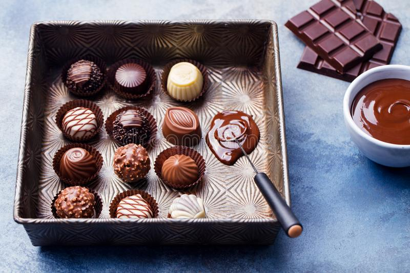 Chocolate candies in a vintage baking dish with chocolatier tool. Close up royalty free stock image