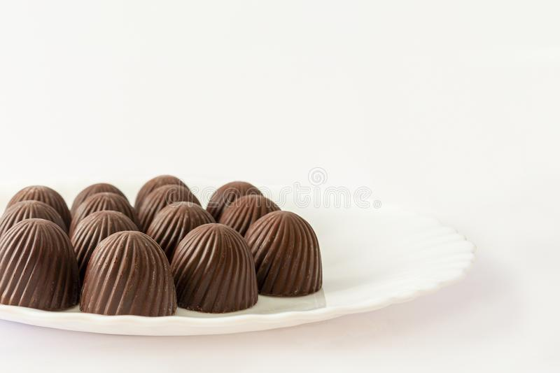 Chocolate candies in a white plate. Image on a white background, copy space royalty free stock photos