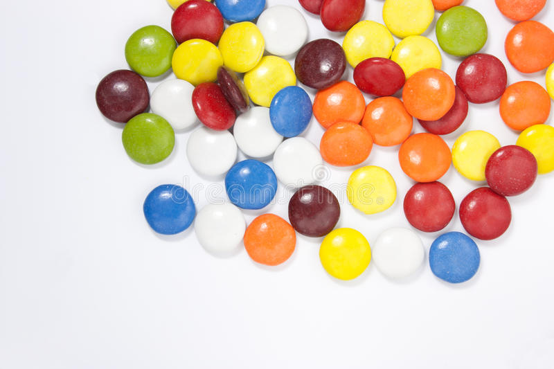 Chocolate candy on white background. Colored chocolate pills stock image