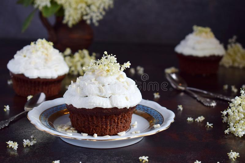 Chocolate capcakes with vanilla cream sprinkled with white chocolate and elderberry flowers. Vintage style. Copy space royalty free stock photo